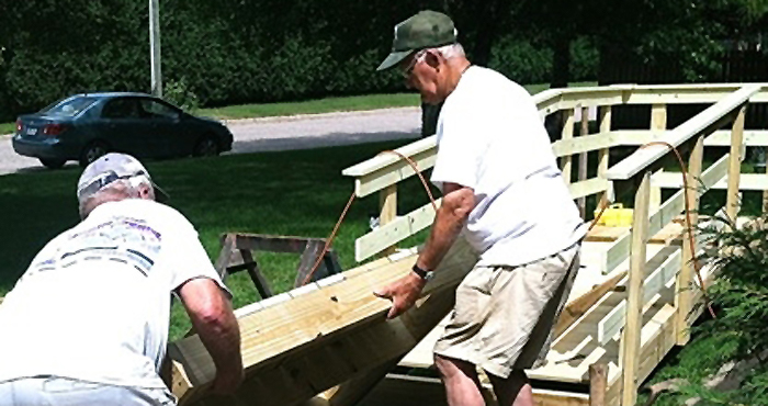 Clintonville Lions Jerry Oestreich and Al Mattson lift a ramp section in place at a recent wheelchair ramp installation.