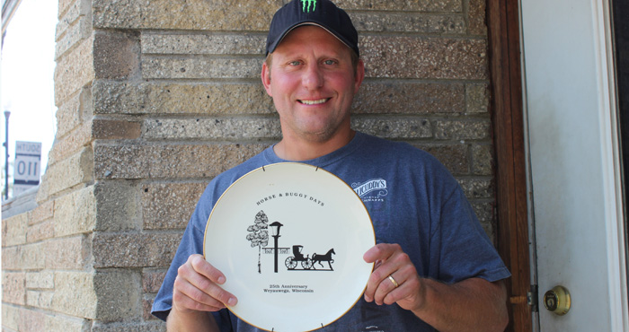 Jered Wilson holds a plate from the 25th anniversary of Weyauwega's Horse & Buggy Days.  Angie Landsverk Photo