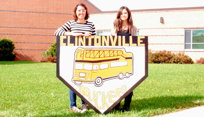 Katherine Edwards and Megan Wittman with the Clintonville wooden shield they created.  Bert Lehman photo