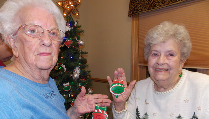 Isabel Janovetz (left) and Carol Lashua collect the ornaments of their loved ones following the Love Lights ceremoney at Iola Living Assistance.  Jane Myhra Photo