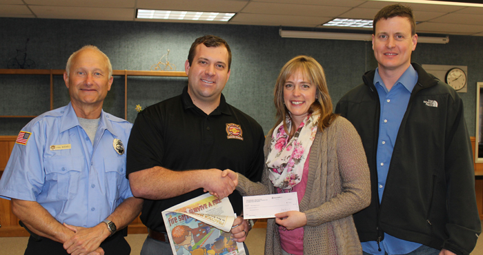 Jenna Zeutzius, a health and social studies teacher at Weyauwega-Fremont Middle School, accepts a $500 grant from Mike Wos, of the Professional Firefighters of Wisconsin Charitable Foundation. Also pictured are Paul Buchholz (left), of the Oshkosh Fire Department and Weyauwega Fire Department, and Greg Stelter (right), of the Oshkosh Fire Department.  Angie Landsverk Photo
