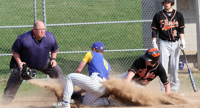 Iola-Scandinavia's Brady Snyder slides safely into home plate underneath Wyatt Erb of Bonduel. Looking on is Snyder's teammate Caleb Loken.  Holly Neumann photo.