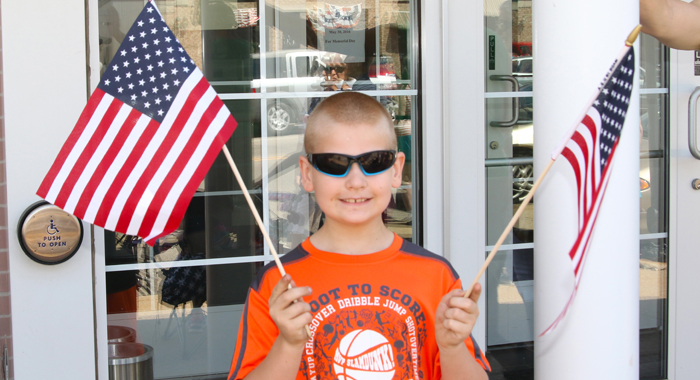 Davis Anderson, 8, proudly waved two American flags during the Memorial Day parade in Iola.  Holly Neumann Photo