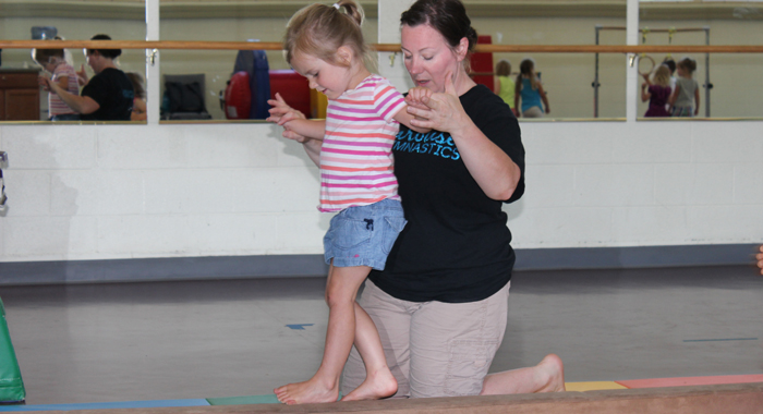 Three-year-old Kendall Rice practices walking backwards with the help of Tiffany Losinski, manager of Carousel Gymnastics, during a June 22 class, at the Waupaca Recreation Center. Angie Landsverk Photo