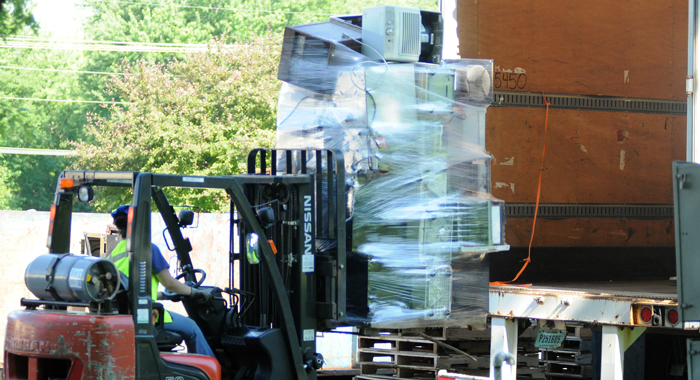 Lora Boeger, a worker with RecycleThatStuff.com, loads a pallet of used dehumidifiers onto a truck at an electronics recycling drive at New London Utilities on Saturday, June 18. Scott Bellile photo