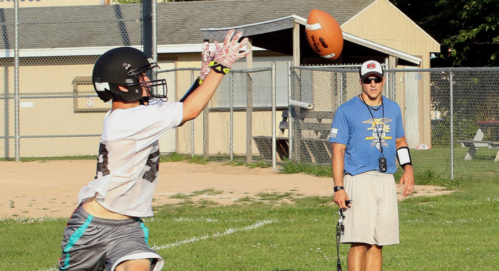 Seth Forbes keeps his eye on the ball while catching a pass at a Manawa football practice. The Wolves have a new coach this year in Brad Johnson. Holly Neumann Photo