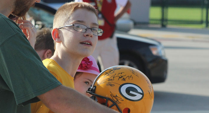 A fan waits to get more autographs on his Green Bay Packers helmet.