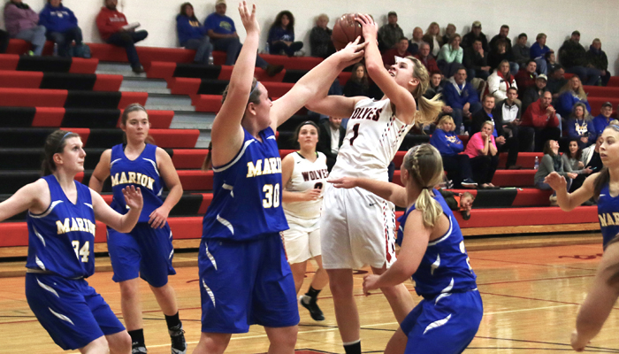 Manawa's Laynie Bessette draws a foul from Marion's Kendra Barrow. Bessette led all scorers with 17 points in the Wolves' 39-30 nonconference win over the Mustangs. Holly Neumann Photo
