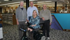 Peg Burington, director of the Waupaca Area Public Library, is seated on the scooter the Mobility 4 Vets Wheelchair Shop donated to the library. Pictured with her are (from left) Jim Peterson, Alan Kjelland and Gene Antoniewicz, who are volunteers with the nonprofit organization. Angie Landsverk Photo