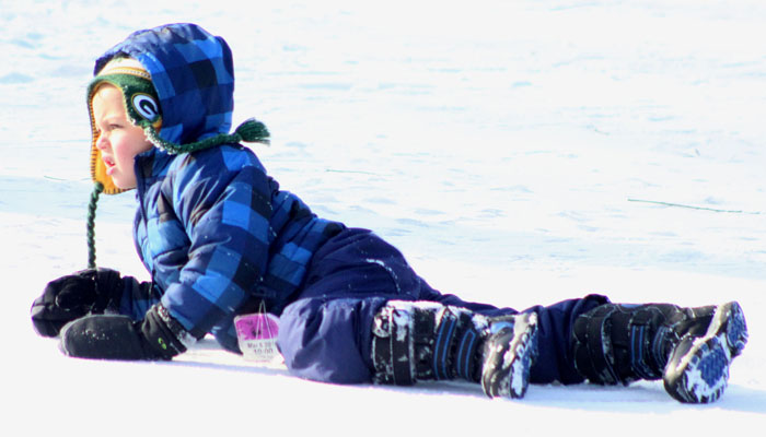 A youngster crawls across the Lime Kiln Lake ice to get a closer view of the Waupaca Polar Plunge Jan. 1. Greg Seubert Photo
