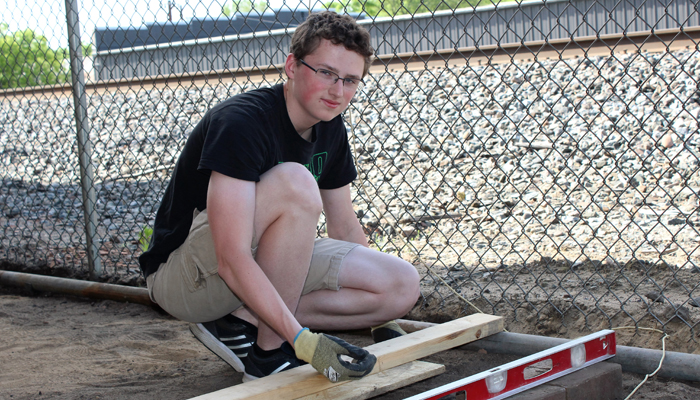 Ryan Hemmila lays a brick platform at the Waupaca Train Depot as part of his Eagle Scout project. Angie Landsverk Photo