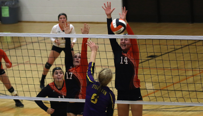 Lindsey Frank, left, and Payton Wester, right get their hands in the air to block a ball hit by Kelsi Schumaker.Holly Neumann photo.