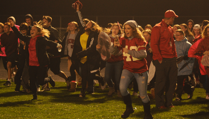 The New London student section races on to the field following the Bulldogs' victory. Erik Buchinger photo